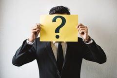 拿着与问号的年轻成人亚洲商人黄色牌纸 免版税库存照片