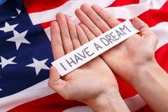 拿着与题字的一个人的手一个标志我有一个梦想 以美国国旗为背景 库存图片