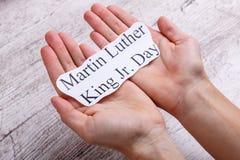 拿着与题字马丁路德金小的一个人的手一个标志 日 免版税图库摄影