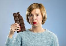 拿着与嘴污点和疯狂的激动的面孔表示的愉快的妇女大巧克力块 库存图片
