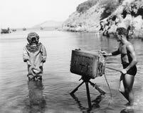 拿着与轻潜水员的一个年轻人的档案一台照相机站立在他前面在海滩(所有人被描述不是lo 免版税库存图片