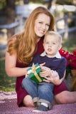 拿着与他的妈妈的年轻男孩圣诞节礼物在公园 免版税库存照片