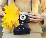 拿着与黄色枫叶特写镜头的秋天照片女性手减速火箭的葡萄酒照相机 图库摄影