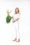 拿着与绿色的白肤金发的妇女新鲜的红萝卜在白色背景离开 女孩吃红萝卜并且稀薄增长 免版税库存图片