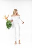 拿着与绿色的白肤金发的妇女新鲜的红萝卜在白色背景离开 女孩吃红萝卜并且稀薄增长 库存照片