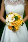 拿着与黄色花的新娘花束 库存照片
