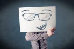 拿着与兴高采烈的面孔的商人一张纸在他的hea前面 免版税库存图片