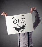 拿着与兴高采烈的面孔的商人纸板对此在前面 免版税库存照片