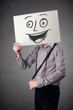 拿着与兴高采烈的面孔的商人纸板对此在前面 库存图片