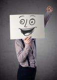 拿着与兴高采烈的面孔的商人纸板对此在前面 免版税库存图片