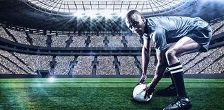 拿着与3d的橄榄球球员画象的综合图象球 免版税图库摄影