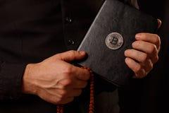 拿着与Bitcoin商标的男性手一部隐藏圣经 免版税库存图片