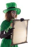 拿着与copyspace的绿色恶鬼女孩一个纸卷,在w 免版税库存照片