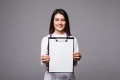 拿着与desease病症文件的年轻女性医生空的文件夹  由笔空白剪贴板的专家点 医疗的妇女 免版税库存照片