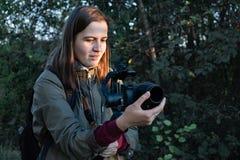 拿着与mirrorless照相机的女性videographer一个常平架 Wom 库存照片