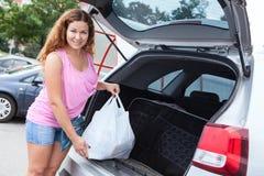 拿着与pov食物neaar树干的俏丽的妇女袋子  库存照片