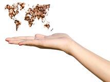 拿着世界地图咖啡豆的女孩手 免版税库存图片