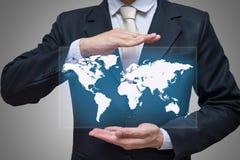 拿着世界地图的商人常设姿势手被隔绝在灰色背景 免版税库存照片