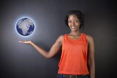拿着世界地球地球的南非或非裔美国人的妇女老师或学生 免版税库存照片