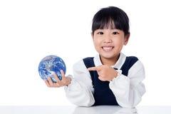 拿着世界地球的亚裔矮小的中国女孩 免版税库存图片