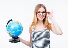 拿着世界地球的玻璃的愉快的女孩 免版税库存图片