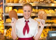 拿着两个不同面包的店主 免版税库存照片