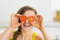 拿着两个切片在眼睛前面的蕃茄的愉快的少妇 免版税库存图片