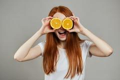 拿着两个切片桔子的愉快的少女在她的在灰色背景的面孔 图库摄影