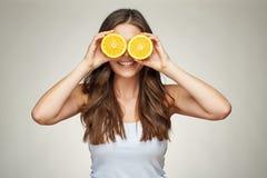 拿着两个半og桔子的微笑的妇女在眼睛前结果实 免版税图库摄影