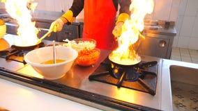 拿着两个平底锅和烹调flambe样式盘的专业厨师在餐馆现代厨房里  男性厨师油煎 股票视频