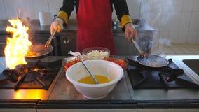 拿着两个平底锅和烹调flambe样式盘的无法认出的厨师在餐馆现代厨房里  男性厨师扔 影视素材
