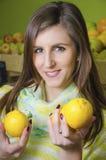 拿着两个柠檬的女孩在蔬菜水果商 免版税库存图片