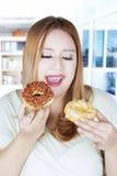 拿着两个油炸圈饼的肥胖妇女 库存照片