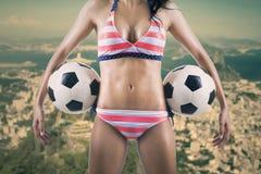 拿着两个球的性感的足球迷 库存图片