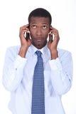 拿着两个电话的商人 免版税库存图片