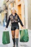 拿着两个绿皮书包裹的愉快的美丽的年轻白肤金发的女孩 免版税图库摄影