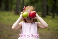 拿着两个苹果的一件桃红色礼服的小红发女孩 库存图片