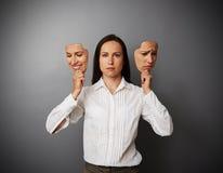 拿着两个面具的女实业家妇女 库存图片