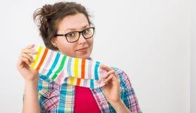 拿着两只五颜六色的袜子的年轻女性 免版税库存照片