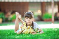 拿着两只春天鸭子的逗人喜爱的女孩户外 免版税库存照片