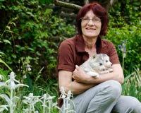 拿着两只西伯利亚爱斯基摩人小狗的妇女 库存图片