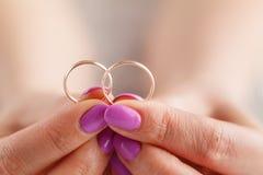 拿着两只金戒指的两只手婚姻 免版税库存图片