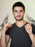 拿着两只鹦鹉的年轻人 免版税库存照片