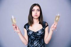 拿着两块玻璃用香槟的年轻美丽的妇女 库存图片