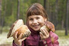 拿着两大白色蘑菇的快乐的女孩 免版税库存照片