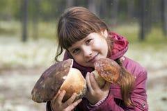 拿着两大白色蘑菇的美丽的女孩 库存图片