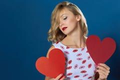 拿着两心脏蓝色背景的白肤金发的妇女 免版税库存图片