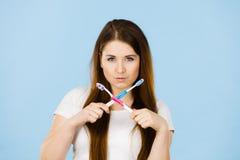 拿着两把牙刷的妇女横渡 库存图片