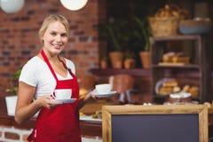 拿着两杯咖啡的俏丽的女服务员 免版税图库摄影