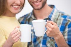 拿着两杯咖啡的微笑的夫妇 图库摄影